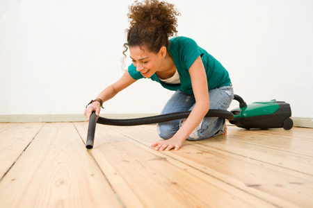 Woman Vacuuming Hardwood Floor